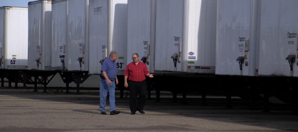 Two men walking past semi trailers