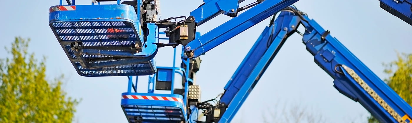 Two blue cherry picker machines