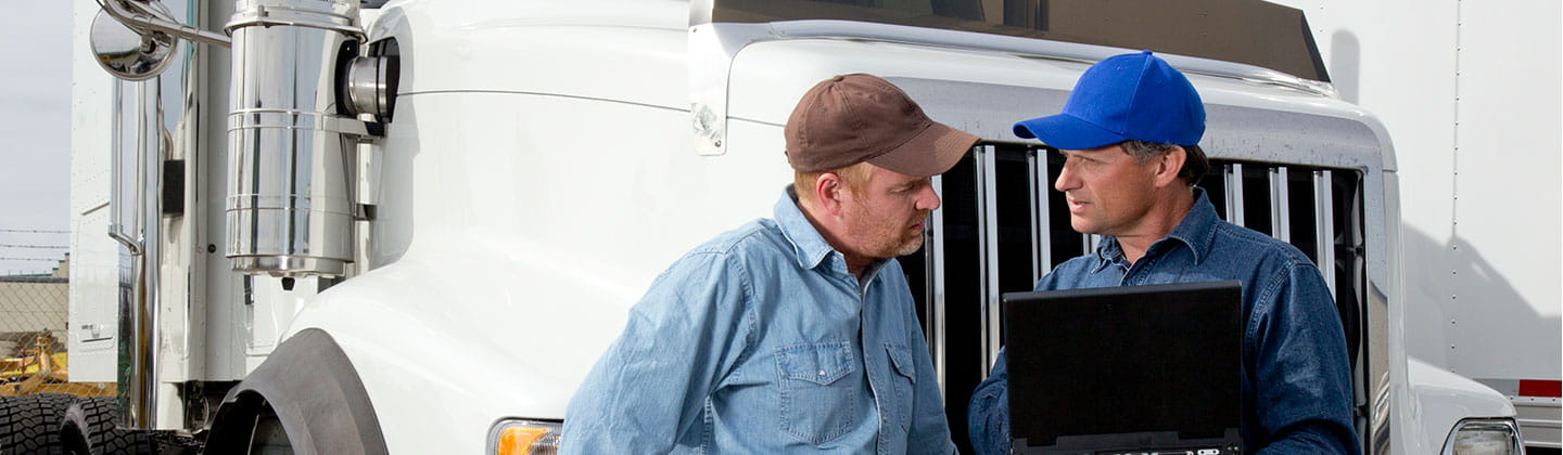 Two men in front of a semi truck